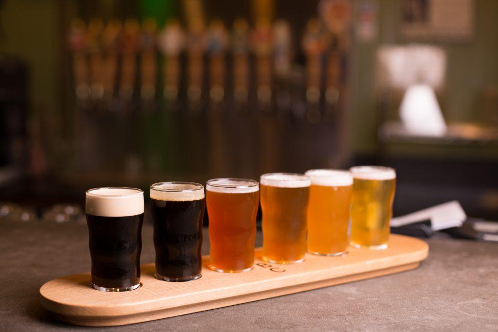 bandeja com cervejas de variedade de arco-íris de malte escuro para hoppy amarelo dourado