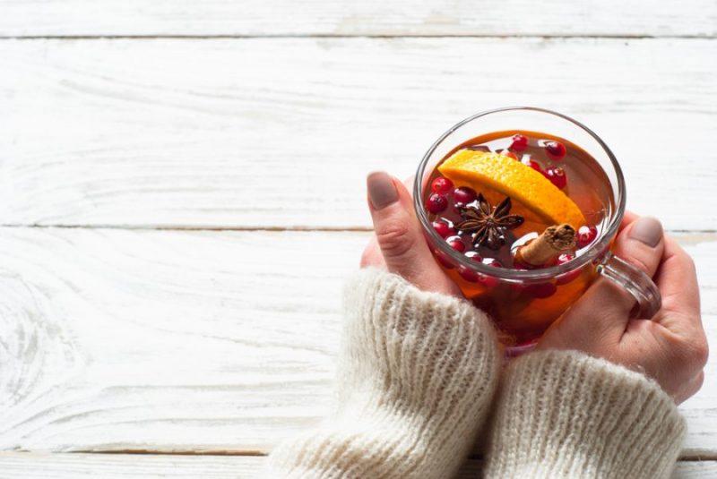 mão segurando uma xícara de chá com frutas, canela e aniz estrelado