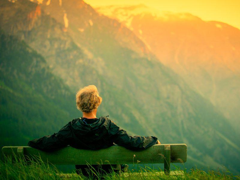 homem sentado refletindo olhando para as montanhas - ansiedade